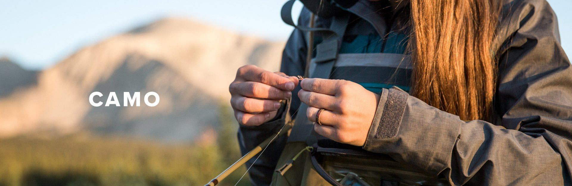 Camo, a woman ties a fly while fishing