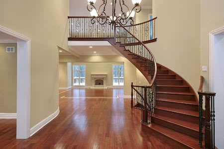 cherry wood foyer with balcony and curved staircase