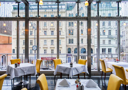 modern seating and table settings in European restaurant overlooking tall buildings