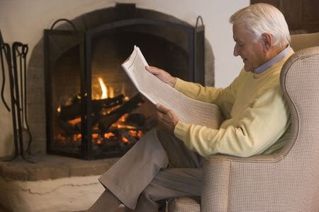 Elderly man in room with fireplace reading a newspaper