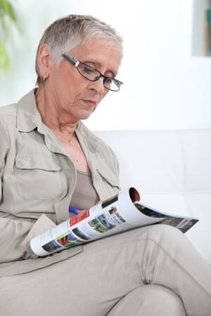 elderly woman sitting in chair with legs crossed reading magazine