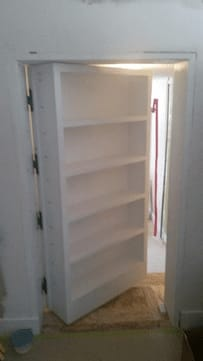 bookcase hanging on Soss Invisible Hinges shown ajar opening outward to show a new room