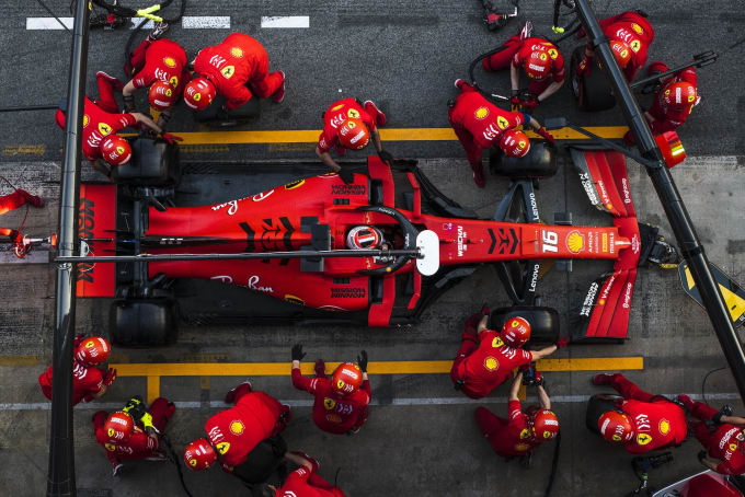 Red Formula 1 race car in the pit with mechanics all around racing to change tires, etc. View from above.