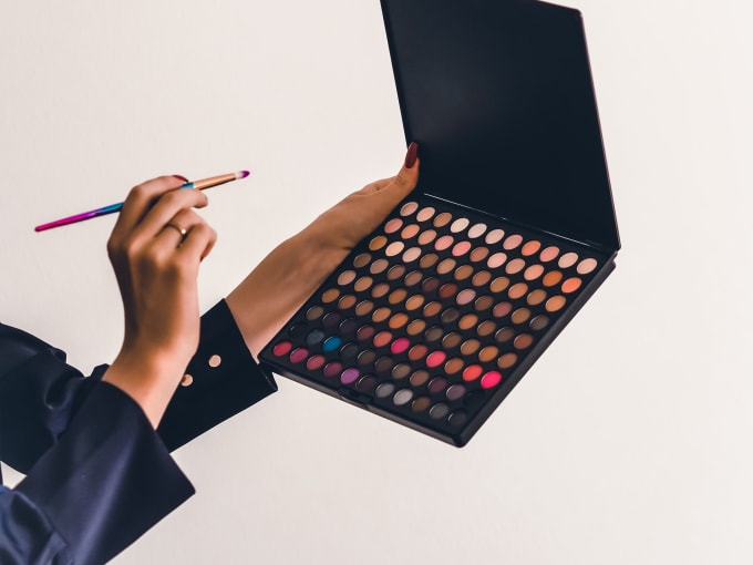 Woman's hand holding a brush up to an eyemakeup palette in the shape of a laptop