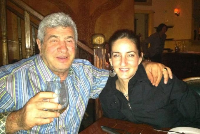 Older man and daughter hugging and holding up a wine glass to the camera