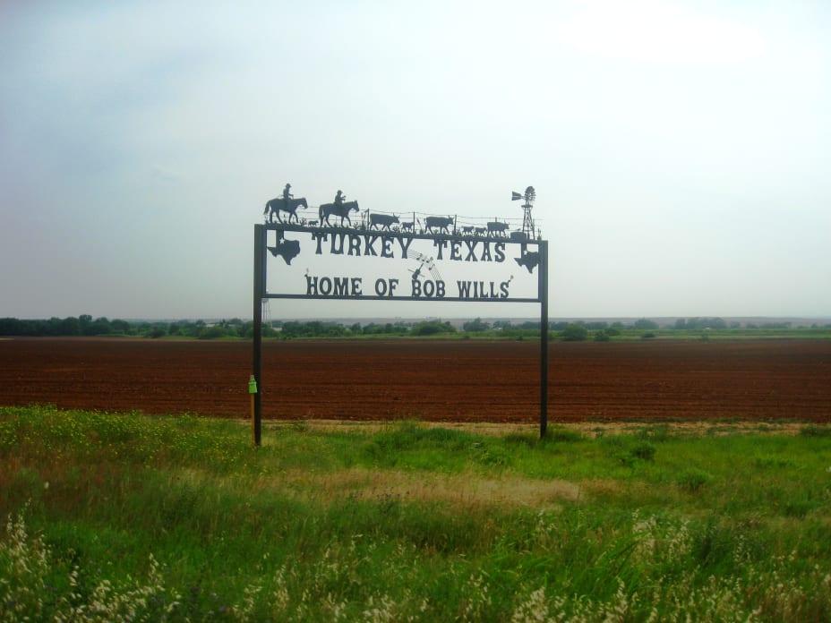 Iron ranch sign saying Turkey, Texas home of Bob Willis on a farm