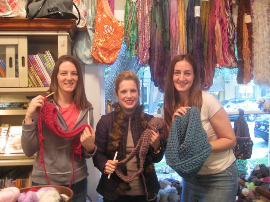 Three women holding up crochet projects in a room surrounded by yarn