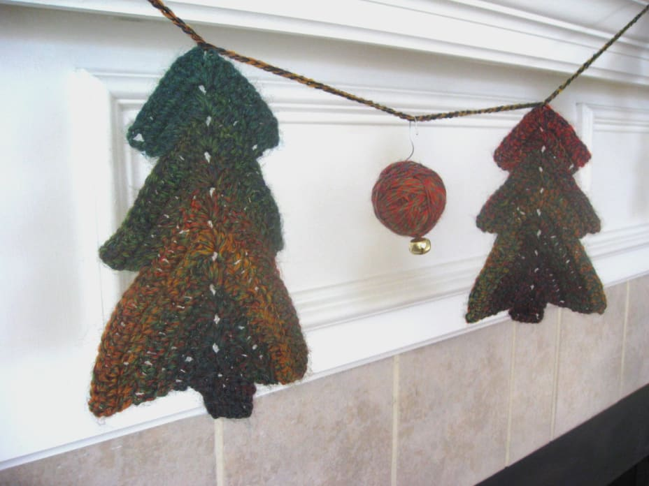Crochet Christmas tree garland with yarn ball ornament hanging from it
