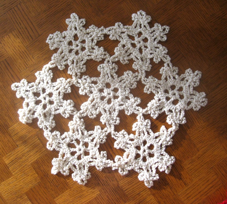 White with gold flecks yarn crocheted into a snowflake shape