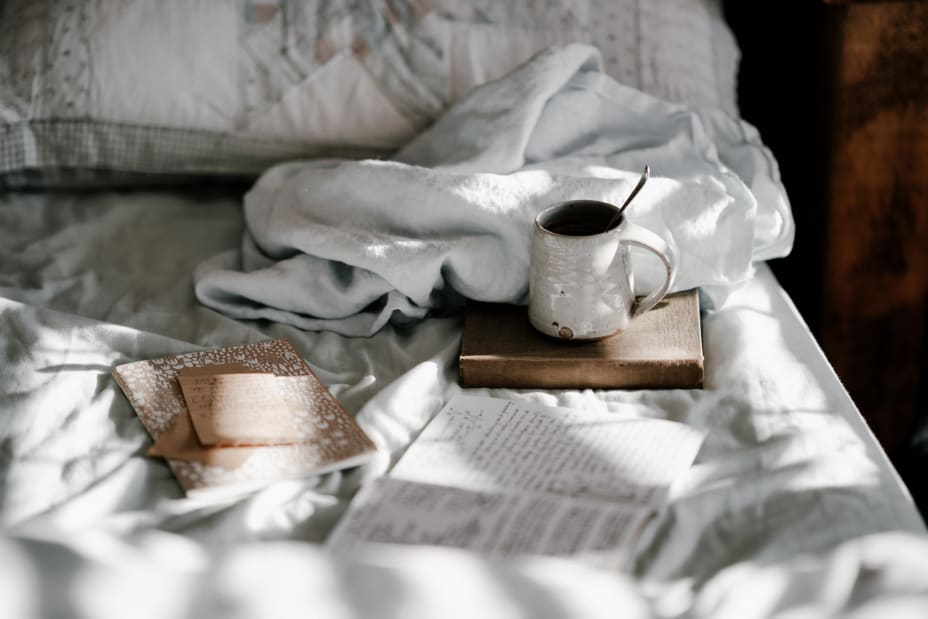 Cup of coffee, book, and journal on slightly messy bed