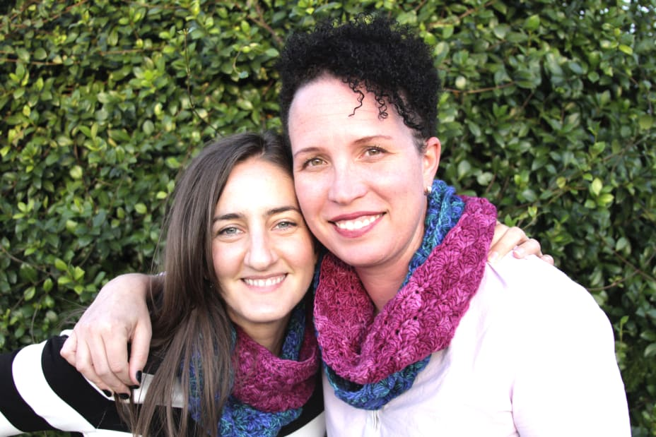 Two friends hugging with matching crochet cowls