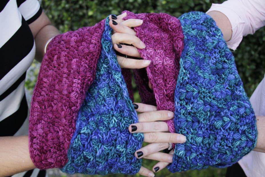 Women holding hands through matching cowls