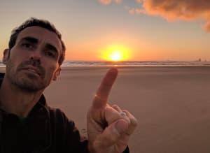 matt pointing at the sun on the oregon coast