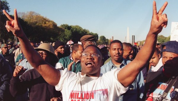 African American man holding up two peace signs at the Million Man March on the National Mall in 1995