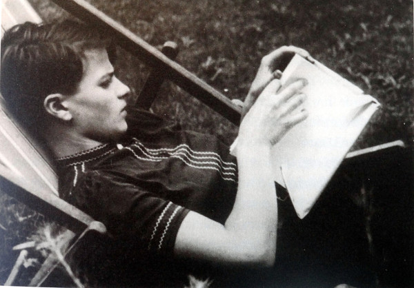 Hans Scholl reclines in a lawn chair reading a book