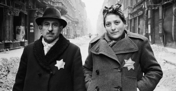 A Jewish man and woman on an empty street looking at the camera with yellow stars on their coats
