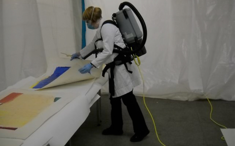 Paintings Conservator Tara Kennedy vacuuming mold off artwork after Hurricane Sandy