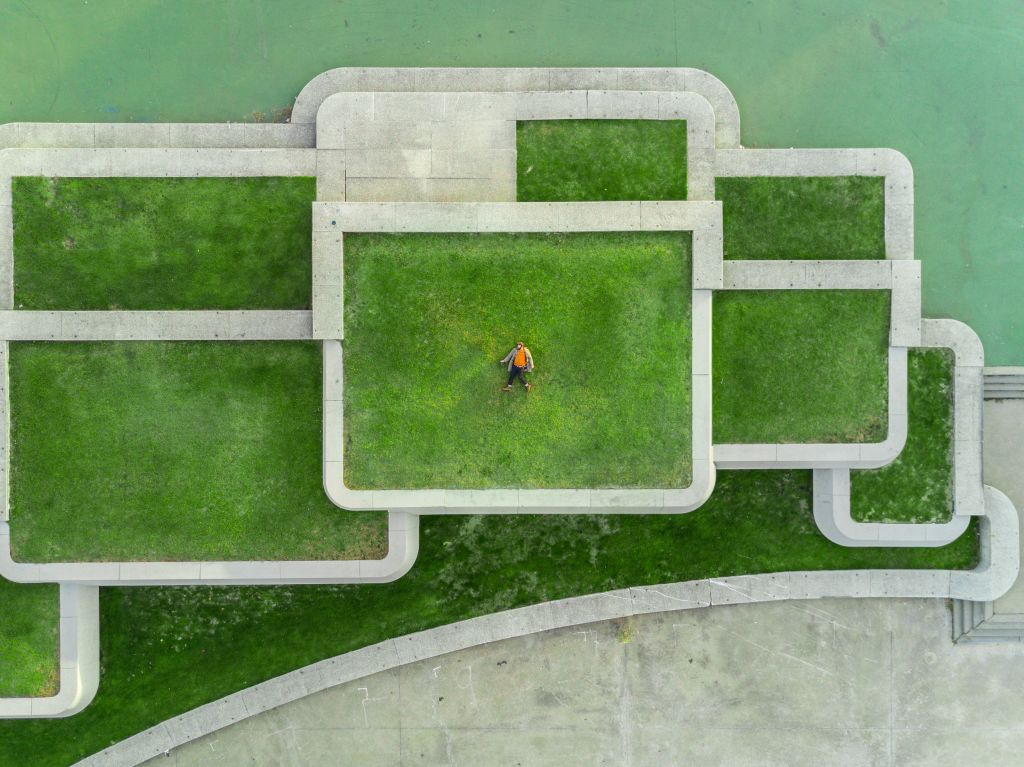 a birds eye view of a person lying in a large rectangular grass area surrounded by other rectangular grass areas