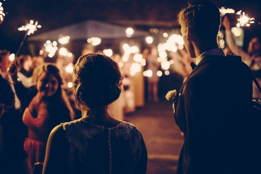 a man and a woman on a wedding at night, turned away from the camera and looking at a smiling woman
