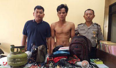 Monang (bukabaju) diapit personel polisi setelah diamankan di Mapolsek Bangun, Minggu 1 Maret 2020.