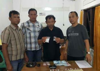 ES alias Iwan Pelangi diapit personel polisi menunjukkan barang bukti narkoba.