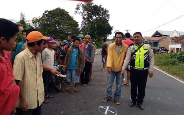 Personel Satlantas dan warga menunjukkan lokasi kecelakaan yang melibatkan Juandi dan Satria di Jalan Siantar-Saribudolok, Minggu (12/5).