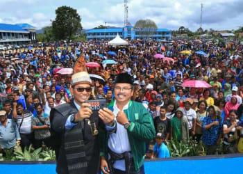 JR Saragih dan Ance Selian, selfi menggunakna kamera hanphone dengan latar belakang ribuan masyarakat pendukung mereka.