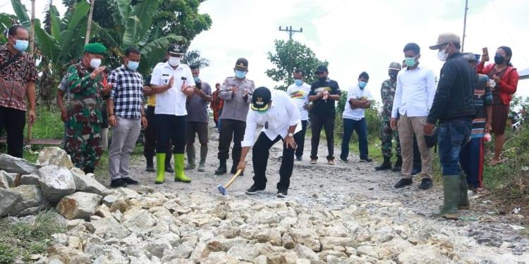 Secara simbolis Bupati memecahkan batu pertama untuk dimulainya marharoan bolon di Nagori Dolok Tomuan.