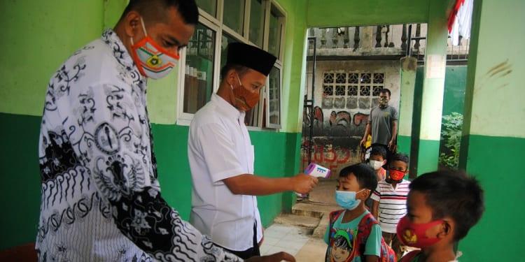 Guru memeriksa suhu tubuh dan menyemprotkan cairan pembersih tangan kepada siswa SD saat mengikuti ujicoba pembelajaran tatap muka di SDN 04 Cihideung Ilir, Ciampea, Kabupaten Bogor, Jawa Barat, Rabu (25/8/2021). Bupati Bogor Ade Yasin mengizinkan sekolah di Kabupaten Bogor untuk menggelar pembelajaran tatap muka pada perpanjangan PPKM level 3 dengan jumlah siswa 50 persen dari kapasitas kelas bagi pendidikan tingkat SD dan SMP serta 33 persen dari kapasitas kelas bagi pendidikan tingkat PAUD. ANTARA FOTO/Arif Firmansyah/hp.