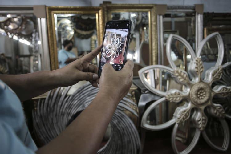 Pedagang cermin memotret salah satu produk yang akan dipasarkannya di aplikasi jual beli di kawasan Pejompongan, Jakarta, Minggu (8/8/2021). Menteri Koordinator Bidang Kemaritiman dan Investasi Luhut Binsar PandjaitanÊmenargetkan pelaku Usaha Mikro, Kecil dan Menengah (UMKM) yang memasarkan produknya di perdagangan digital (e-commerce) pada tahun 2023 sebanyak 30 juta pelaku usaha. ANTARA FOTO/Dhemas Reviyanto/wsj.