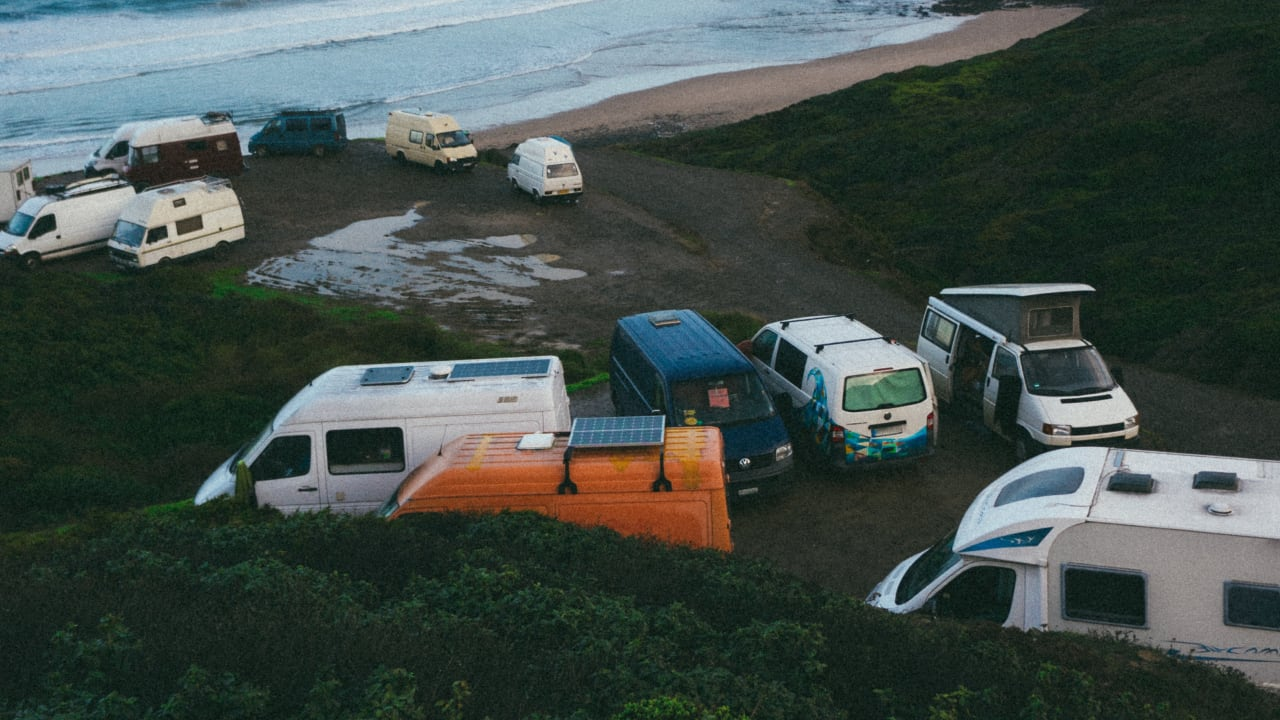 Campervans with solar panels on the roof parked at the beach.