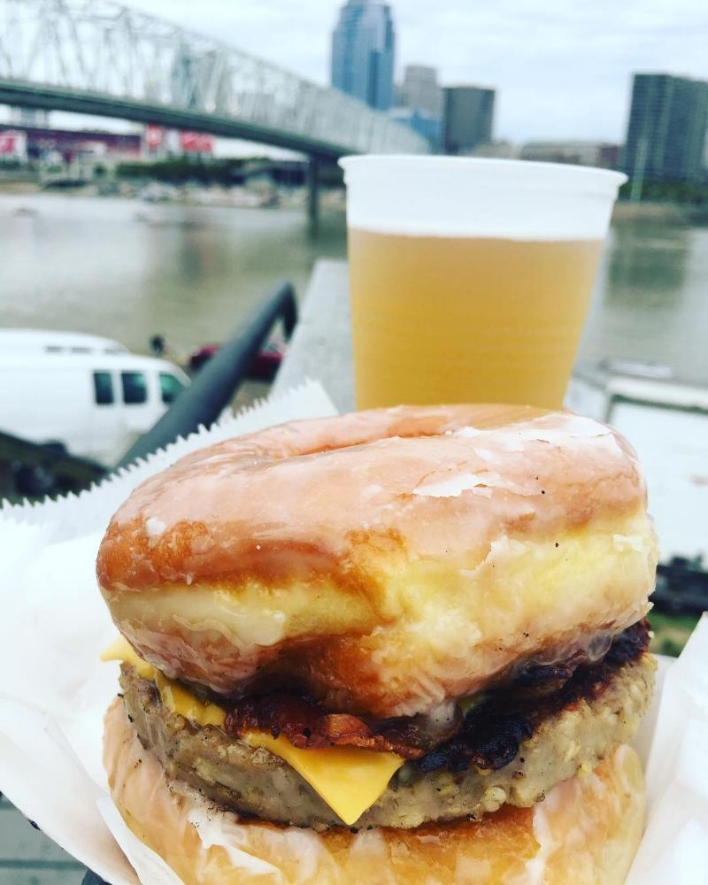 Goetta donut sandwich with a plastic glass filled with beer and a bridge in the background