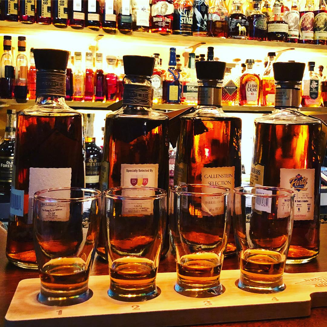 Four bottles of bourbon on bar in front of Prohibition Bourbon Bar's huge bourbon collection