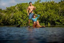 Family time paddle boarding oin Daytona Beach