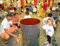 Photo of Mom, Dad and little girl paining barrel