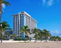 Beach view of the Westin Fort Lauderdale Beach REsort with palm trees.