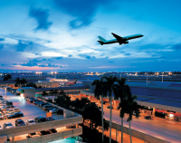 View of the Fort Lauderdale-Hollywood International Airport with a plane taking off at dusk over palm trees.