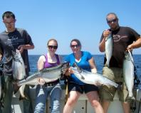 Loyal customers Bobby and Kelsey Ostman (left) and Jessica and Zach Leclair return to Oswego County year after year to fish Lake Ontario for king salmon with Capt. Ed Monette of Cannonball Runner Charters, Oswego. King salmon dominated the Lake Ontario catch in the summer of 2012, according to the New York State Department of Environmental Conservation. (Photo courtesy of Capt. Ed Monette.)