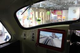 View from the inside of a locomotive engine, with a screen showing a train on tracks below the window.