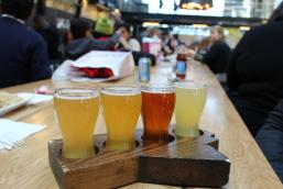 Four glasses of beer sit on a wooden paddle shaped like Manitoba, on a long wooden table.