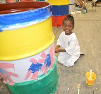 photo of little girl painting barrel
