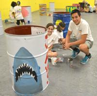 Photo of two teens painting Jaws on Barrel