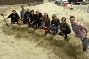 The Eugene, Cascades & Coast staff proudly shows their sand creations, with animals, sports themes, and more