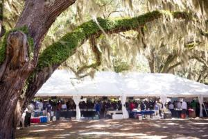 An outdoor tent covers the Grand Oaks Tasting Tour event at the St. Simons Island Food & Spirits Festival on St. Simons Island