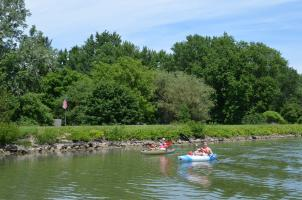 Kyakers wave to tour boats on the Erie Canal in Rochester, NY
