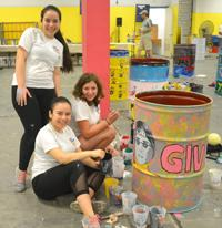 Photo of three girls with painted can featuring John Lennon