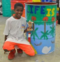 Photo of young man sitting by his painted barrel