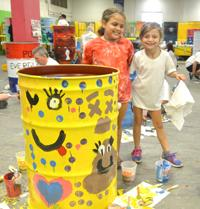 Photo of two little girls paining a barrel