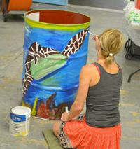 Photo of women painting a turtle on barrel