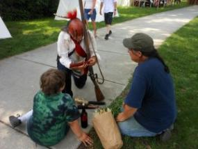 An American Indian interpreter discusses corn with two  visitors at the Siege of 1812